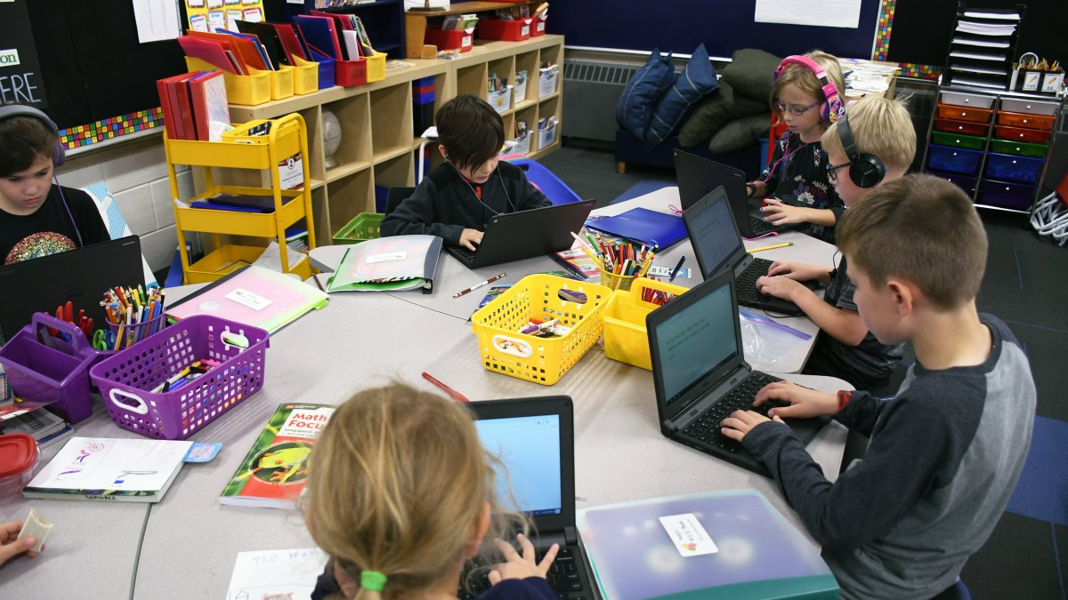 Students work on laptops at a group desk